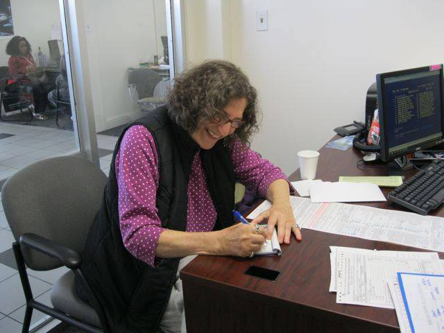 Car Pal client signs her paperwork for a vehicle at a Subaru dealership in Berkeley, CA