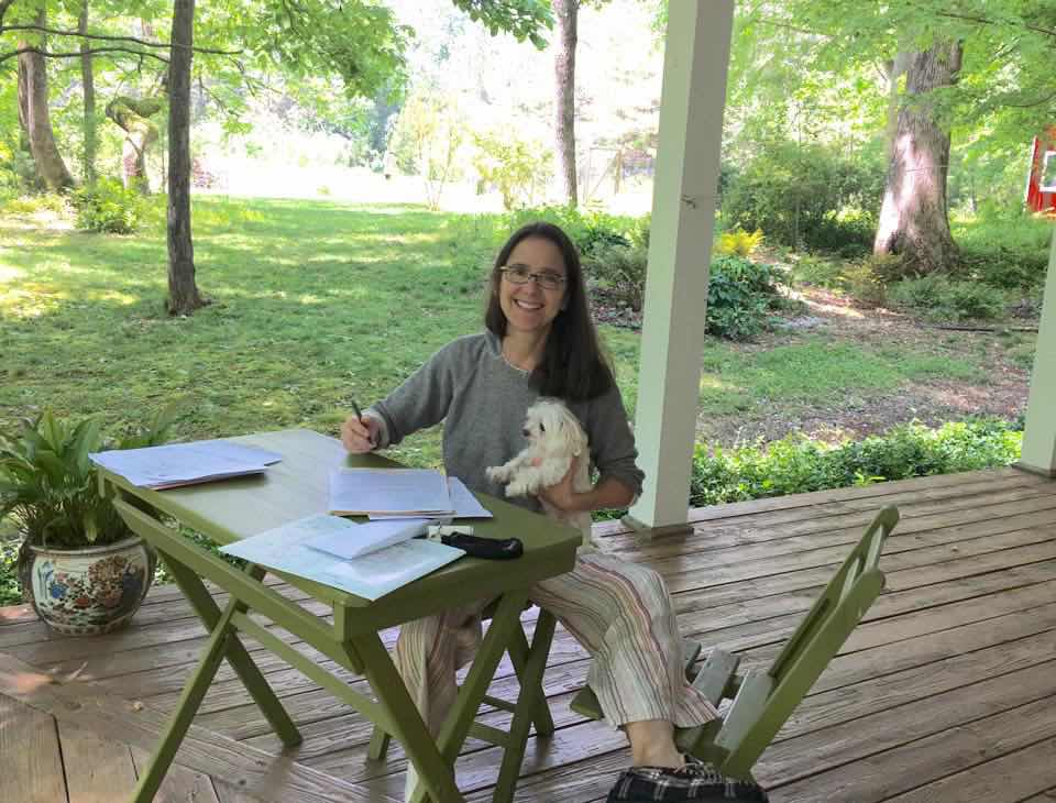 Car Pal founder and CEO S. Lindsay Graham at table on porch with home vehicle delivery paperwork on table and small white Maltese dog on her lap.