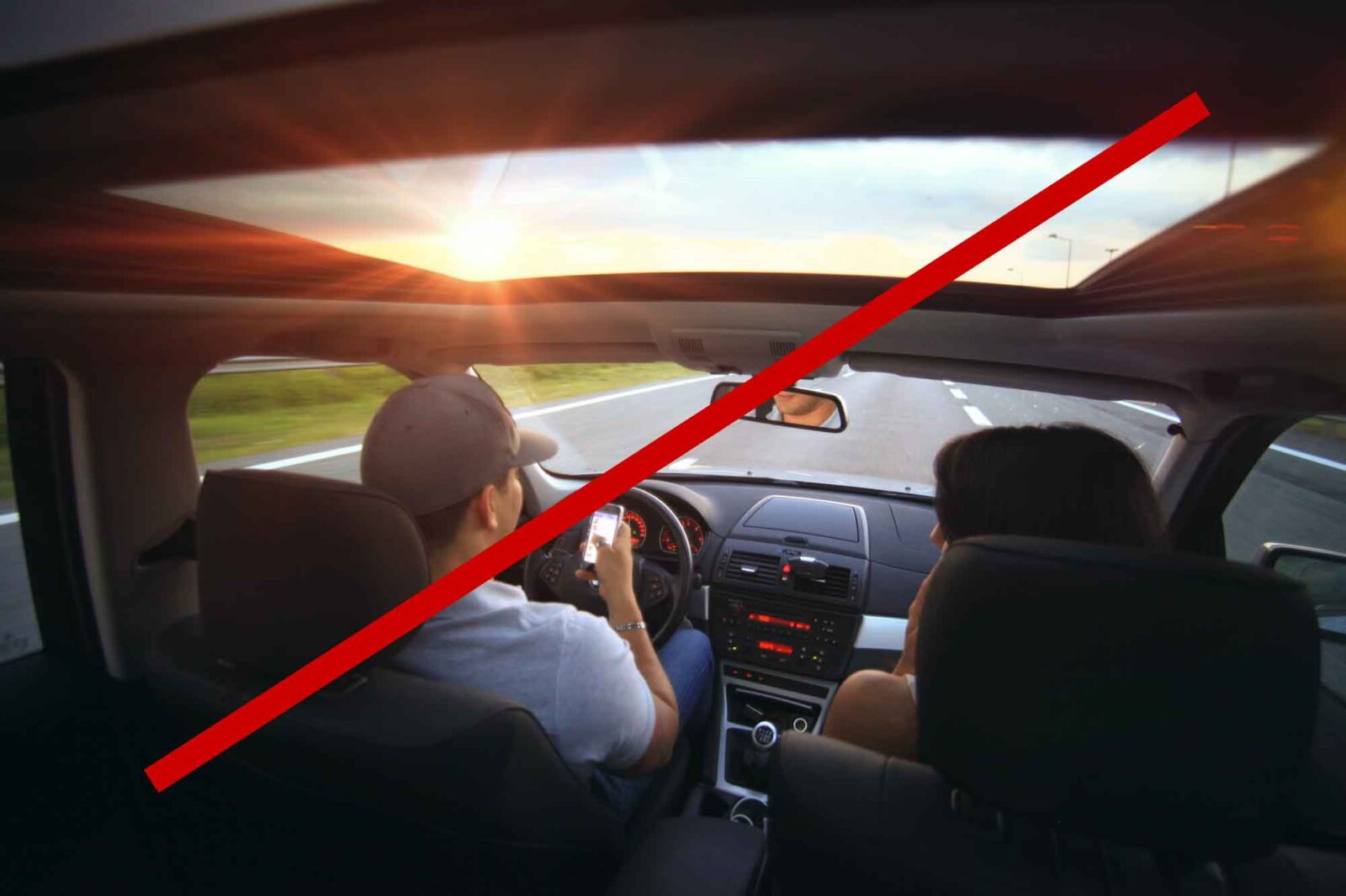 Image of a man texting while driving for article called The Lowdown On Auto Insurance in 2021 and How To Steer Clear of Steep Rate Increases.